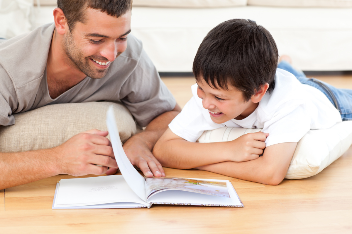 Cute boy reading a book with his father on the floor